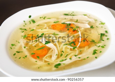 A close-up of a bowl of traditional chicken soup served in a white bowl - stock photo