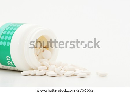 A close up of a box of pills, pills pouring out, shot on white