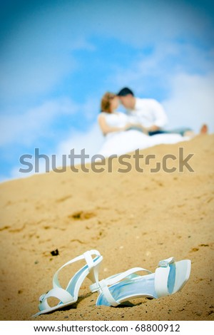 A close up of a bride's wedding shoes on the sand at the seaside with the couple in the background, focus on the shoes in front. - stock photo