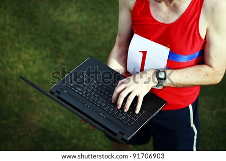 A close up of a businessman dressed in running attire with the number one on his chest, working on his laptop outside. - stock photo