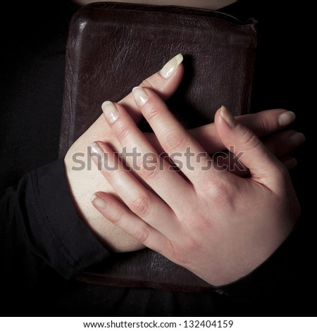 A close-up of a christian woman pray. Holding a Cross over a bible. Toned.