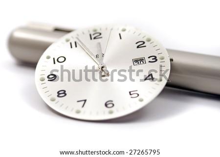 A close up of a clock face resting on an off-focus pen.