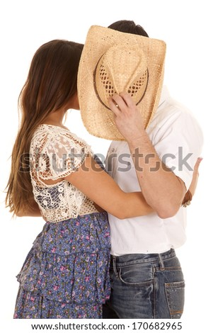 A close up of a cowboy kissing a girl behind his hat. - stock photo