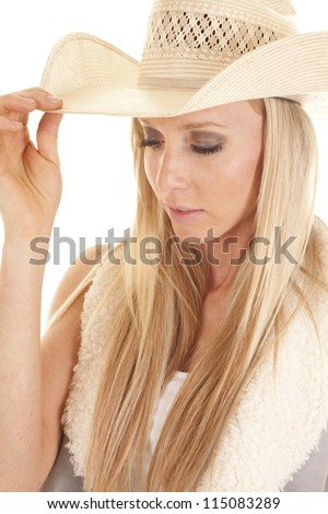 A close up of a cowgirl looking down holding on to the brim of her straw hat. - stock photo