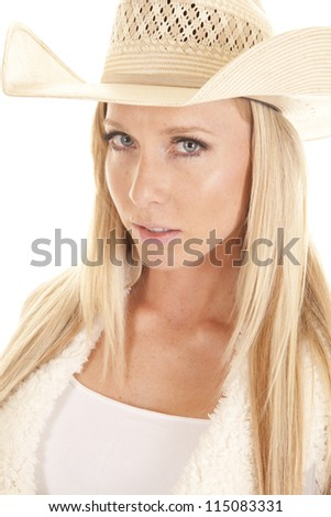 A close up of a cowgirl with a serious expression on her face wearing her straw hat. - stock photo