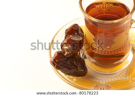 A close up of a cup of arabic tea and dates - stock photo