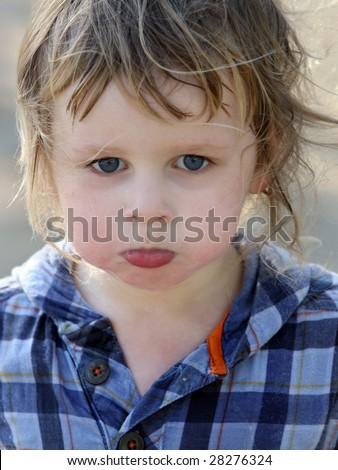 A close-up of a cute sad baby boy - stock photo