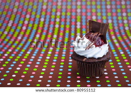 A close up of a dark chocolate cupcake with a polkadot background. - stock photo