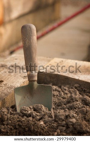 A close-up of a dirty old trowel standing in the earth - stock photo