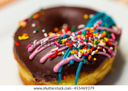 A close up of a doughnut with chocolate icing, colorful sprinkles, and drizzled blue and pink icing. - stock photo