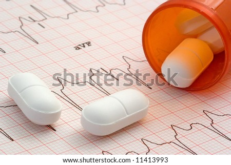 A close up of a EKG with a bottle of pills sitting on it. - stock photo