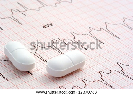 A close up of a EKG with pills sitting on top of it. - stock photo