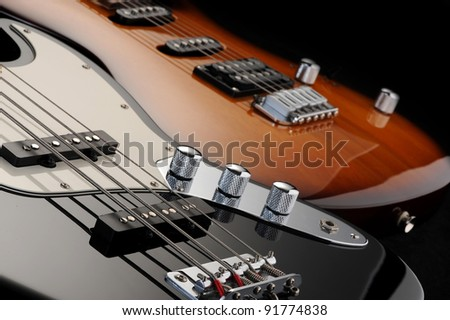 a close up of a electric guitar , and  of a black bass glossy on dark background - stock photo