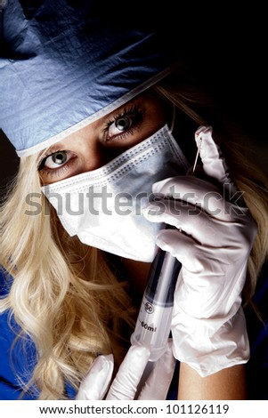 A close up of a female doctor with a huge needle. - stock photo