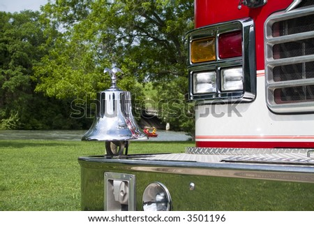 A close up of a fire truck's bell and front bumper with the rescue team performing a water rescue drill in the background. - stock photo