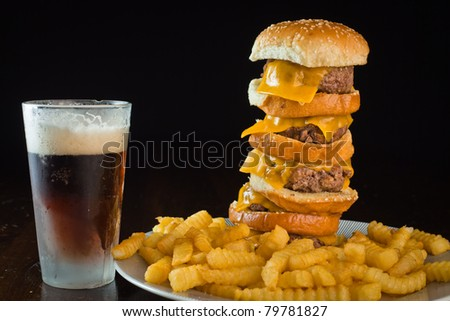 A close up of a five patty cheese burger with fries and a beer. - stock photo