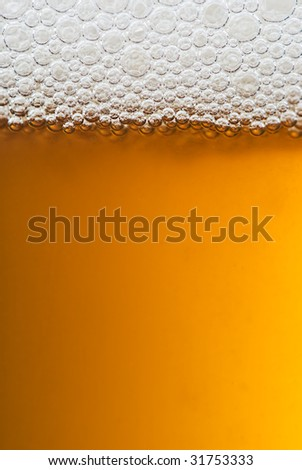 A close up of a glass of beer with lovely amber colour and white frothy bubbles on top. - stock photo