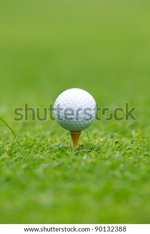 A close-up of a Golf ball sitting on a tee - stock photo