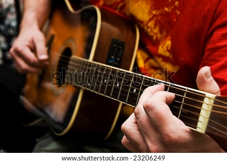 A close up of a guitarists hands playing acoustic guitar. Narrow depth of field. - stock photo