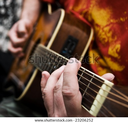 A close up of a guitarists hands playing acoustic guitar. Narrow depth of field.