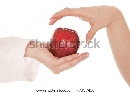 A close up of a hand getting ready to grab an apple from another person.