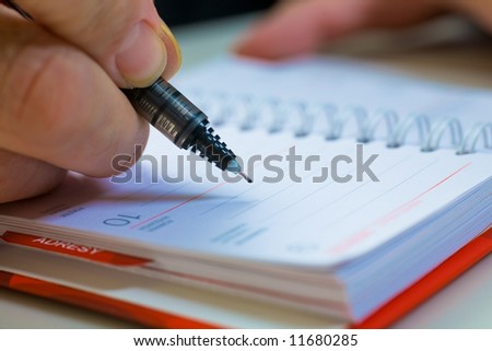 A close up of a hand of the businessman with the pen. Shallow depth of field - stock photo