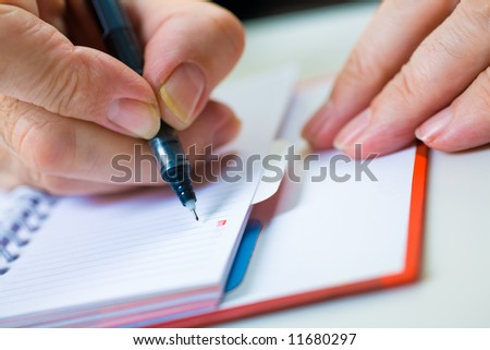 A close up of a hand of the businessman with the pen. Shallow depth of field