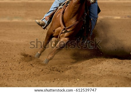 A close up of a horse and rider with dirt flying.