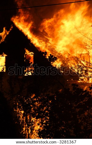 A close-up of a house fire and the shell of the house burning - stock photo