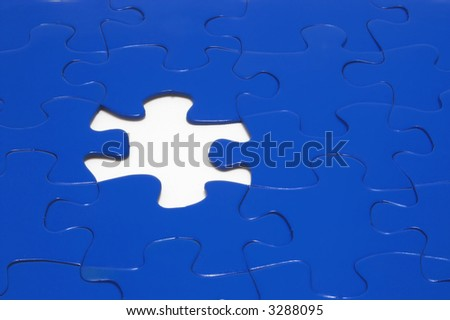 A close-up of a jigsaw puzzle with a missing puzzle piece.