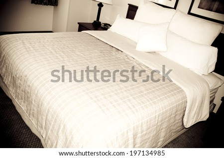 A close-up of a made-up bed in a hotel room. - stock photo