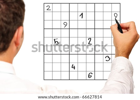 A close up of a male hand solving sudoku over white background - stock photo