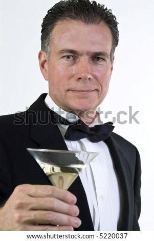 A close up of a man's hand who is dressed in formal attire and holding a martini glass. - stock photo