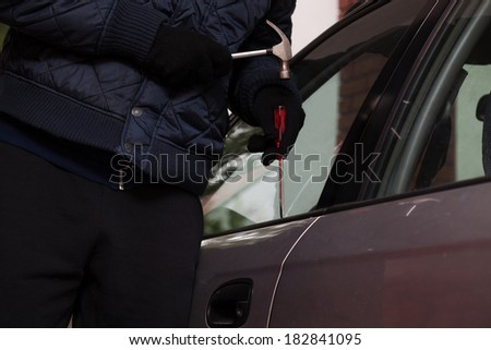 A close-up of a man trying to break in a car