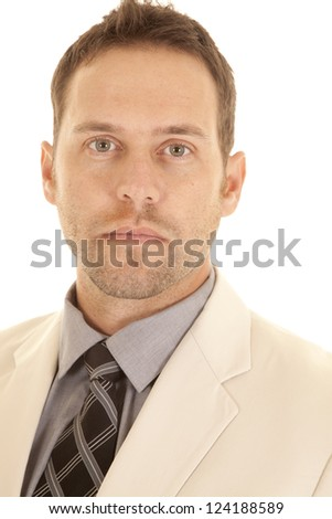 A close up of a mans face with a serious expression on his face, in his suit and tie. - stock photo