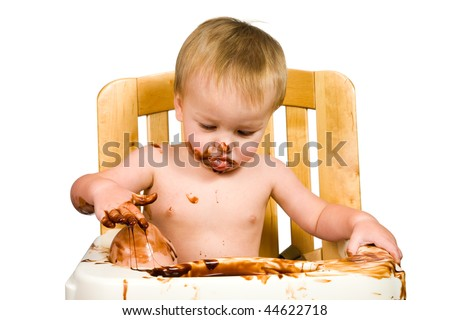 A close up of a messy baby eating chocolate. - stock photo