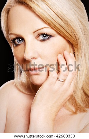 A close up of a middle aged woman wearing a diamond ring, looking at the camera. - stock photo