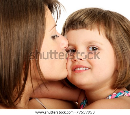 A close-up of a mother kissing her baby girl over white background - stock photo