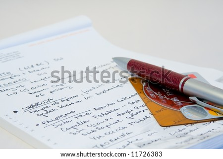 a close-up of a notebook, credit card and a pen