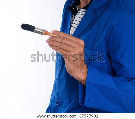 A close up of a painter wearing a blue jumpsuit with a black bristled brush in his right hand. - stock photo