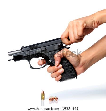 A close up of a pair of hands cocking a black handgun. The bullet can be seen inside the gun.. - stock photo