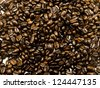 A close-up of a pile of coffee beans to show oily texture. - stock photo
