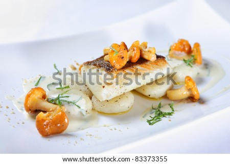 A close-up of a portion of fish with chanterelle mushrooms served with sauce on a white plate - stock photo
