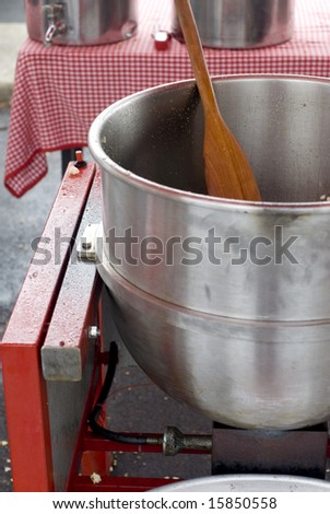 A close up of a pot and wooden spoon for popping sweet kettle corn.