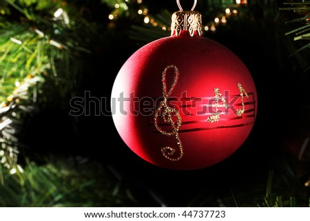 A close up of a red christmas bauble with musical notes. - stock photo