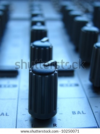 A close up of a row of mixer knobs in a blue nightly light. - stock photo