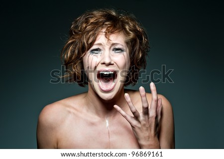 a close up of a screaming and crying young female - stock photo