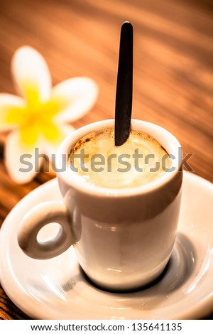 a close-up of a single macchiato stirred on a wooden table with a frangipani in the backround - stock photo