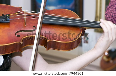 A close up of a violin or fiddle player strumming her violin or fiddle. - stock photo