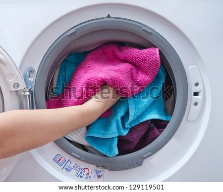 A close up of a washing machine loaded with clothes - stock photo